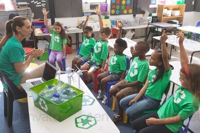 School kids wearing recycle tee-shirt raising hand to answer at a question asking by their teacher