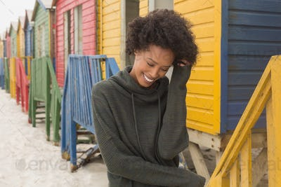 Woman with hand in hair standing at beach hut