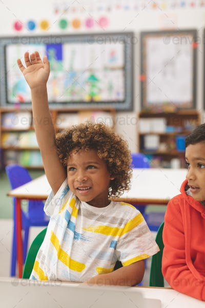 Schoolboy raising his hand in with his friend next to him in classroom at school