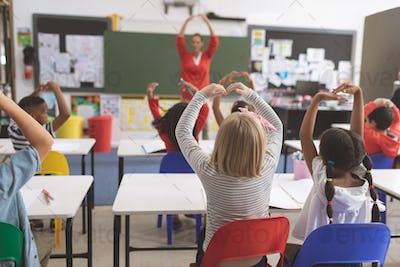 Rear view of mixte ethnicity school kids with arms up playing in the classroom at school