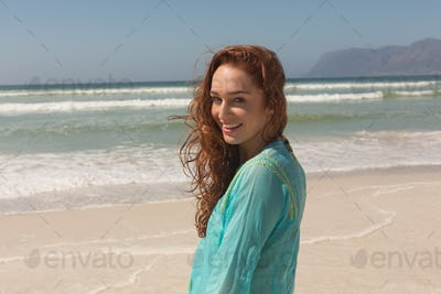 Portrait of happy beautiful young woman looking at camera standing on the beach. She is smiling