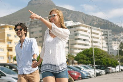 Caucasian couple walking hand in hand and interacting on the promenade on a  sunny day.