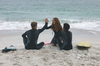 Friends sitting and interacting with each other while giving high five on beach
