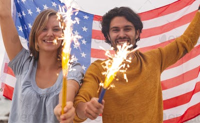 Couple playing with fire cracker while holding american flag. They are smiling and looking at camera