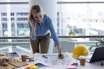 Female architect talking on mobile phone while working at desk in modern