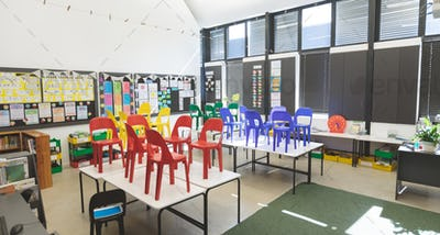 Front view of color chairs arranged on table in empty classroom at school