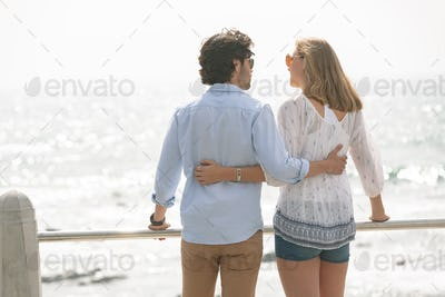 Rear view of young Caucasian couple standing near sea side at promenade on a sunny day