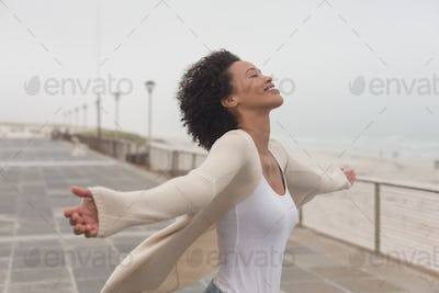 Happy young African American woman with arms stretched out standing at promenade
