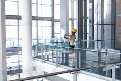 Side view of young African-American female architect looking at blueprint in modern office