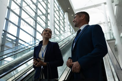 Businessman and businesswoman interacting with each other near escalator in office
