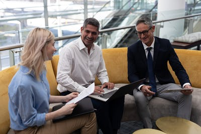 Business executives interacting with each other sitting on the sofa in modern office