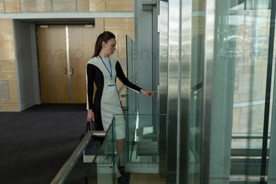 side view of beautiful toung Caucasian female executive standing near elevator in modern office