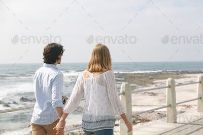 Couple walking hand in hand on the promenade at the seaside