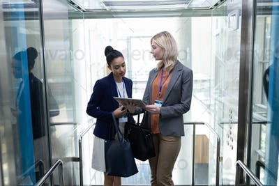 Businesswomen discussing over digital tablet in modern office elevator