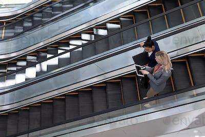 Businesswomen discussing over digital tablet on escalator in modern office