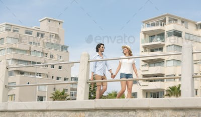 Low angle view of young Caucasian couple walking on the promenade at the seaside. They are smiling
