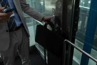 Mid section of Caucasian businessman using mobile phone in the elevator at office