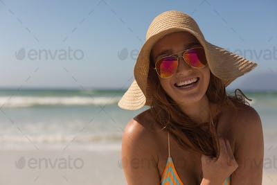 Pretty happy young Caucasian woman in bikini with hat and sunglasses looking at camera on the beach