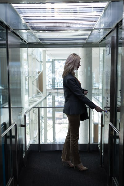 Side view of pretty young blonde Caucasian businesswoman using elevator in modern office