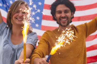 Young Caucasian couple playing with fire cracker while holding american flag.