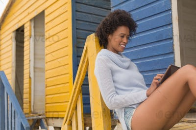 Pretty young African American woman using digital tablet sitting on the beach hut.