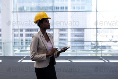 Female architect with digital tablet standing in modern office