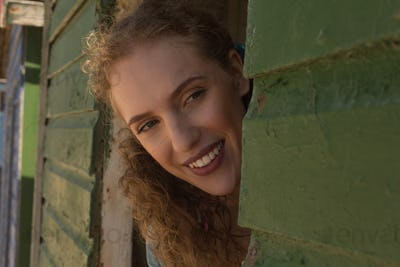 Close-up of happy gorgeous young Caucasian woman looking away from beach hut. She is smiling