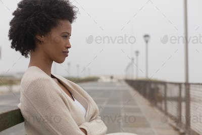Side view of thoughtful young African American woman sitting on bench at promenade