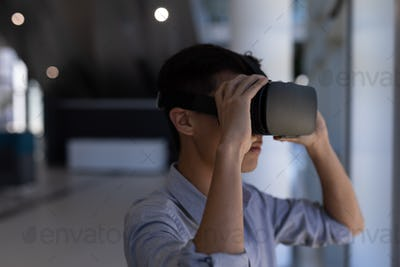 Side view of young Asian male executive using virtual reality headset standing in modern office