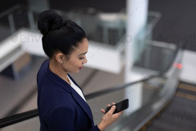 Side view of pretty young mixed-race businesswoman using mobile phone on escalator in modern office
