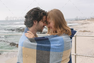 Happy young Caucasian couple wrapped in blanket standing at promenade near beach on a sunny day.