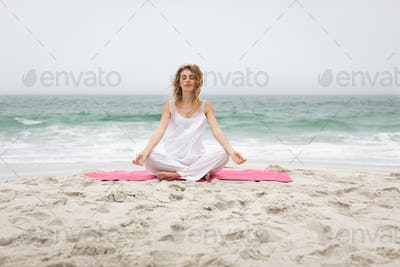 Front view of beautiful caucasian woman performing yoga at beach on sunny day
