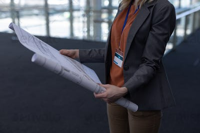 Mid section of young blonde Caucasian female architect holding blueprint in modern office