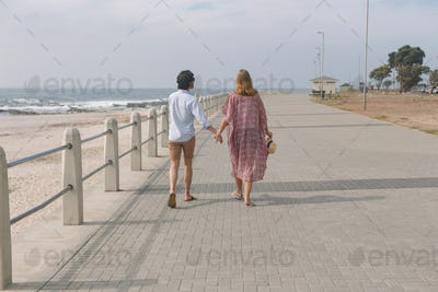 Rear view of young Caucasian couple walking on the promenade at the seaside on a sunny day