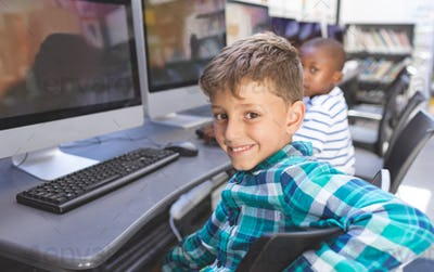 Portrait of happy caucasian schoolboy sitting on chair and looking at camera  in computer room