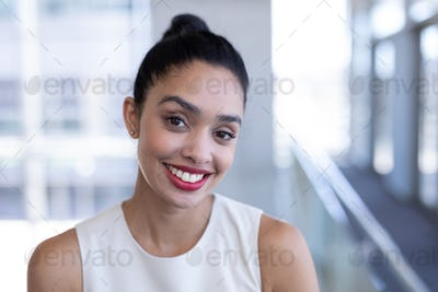 Portrait of happy young mixed-race businesswoman looking at camera in modern office