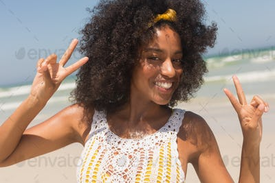 Front view of happy young African American woman showing victory sign standing on the beach