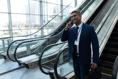 Caucasian businessman talking on mobile phone while moving down on escalator in office lobby