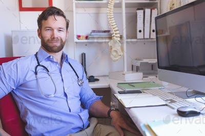 Portrait of confident Caucasian male doctor sitting in clinic