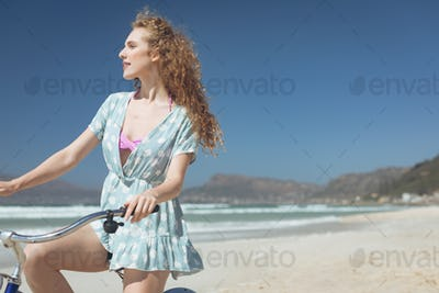 Side view of thoughtful Caucasian woman riding bicycle at beach on a sunny day. She seems happy