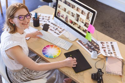 Young Caucasian female graphic designer working on graphic tablet at desk in office.