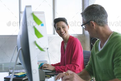 Side view of Multi-ethnic business people discussing over computer at desk in modern office