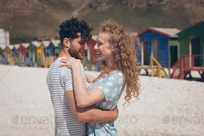 Side view of romantic Caucasian couple dancing at beach on a sunny day. They are smiling