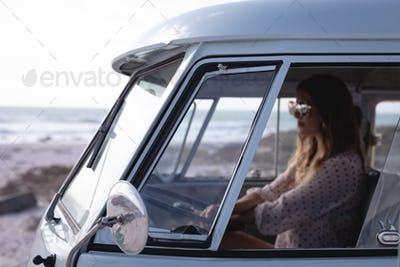 Side view of beautiful Caucasian woman driving camper van at beach on a sunny day