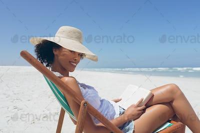 Woman sitting on sun lounger at beach