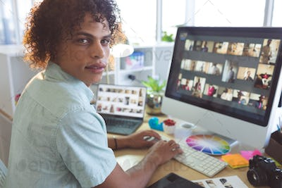 Handsome mixed race male graphic designer looking at camera while working on computer