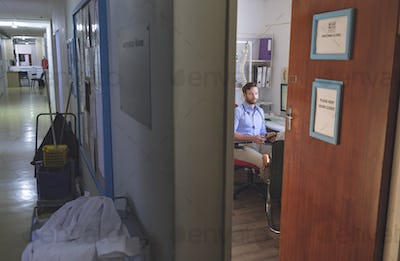 Front view of a Caucasian male doctor interacting with patient inside clinic room