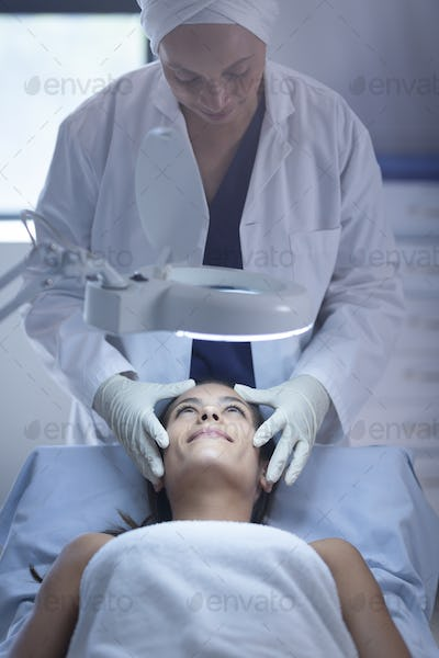 Front view of a female surgeon examining her Caucasian patient during plastic surgery in clinic