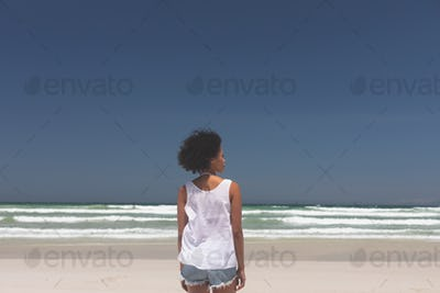 Rear view of beautiful young mixed-race woman standing at beach on a sunny day. She is looking away