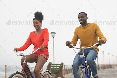Front view of cute happy Multi-ethnic couple riding bicycle at promenade on a sunny day